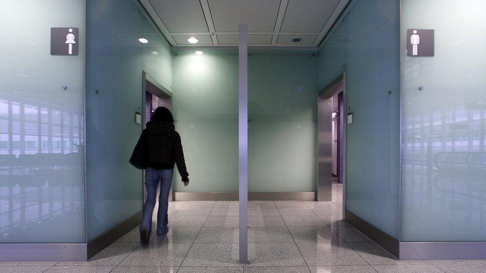 A woman walks into a public toilet