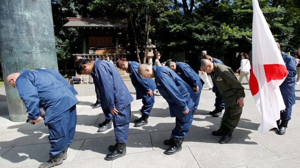 Members of a right-wing group bow their heads to honour the war dead at the shrine