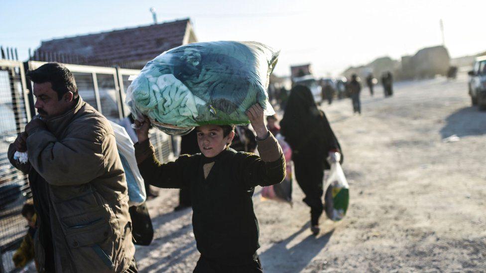 A Syrian boy holds his belongings above his head at a Turkish border crossing