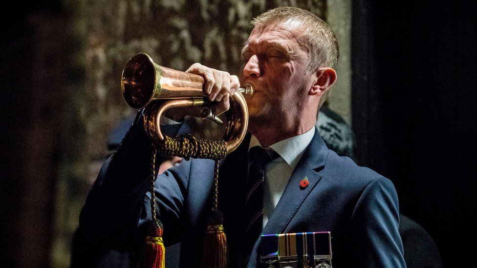 Bugler Noel Trimble plays The Last Post during a dawn Armistice Day ceremony at Enniskillen Castle in County Fermanagh