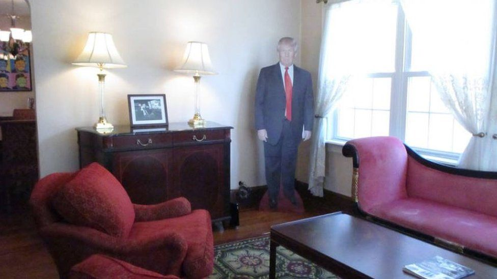 A life-size cutout of the president sits in the living room