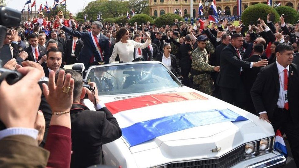 Mario Abdo Benitez and his wife Silvana Lopez wave to the crowds from a 1967 Cadillac convertible after the swearing-in ceremony at the presidential palace in Asuncion.