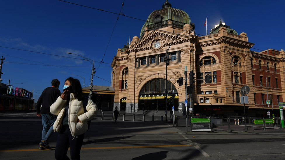 Person wearing a mask walks past a deserted Flinders Street Station