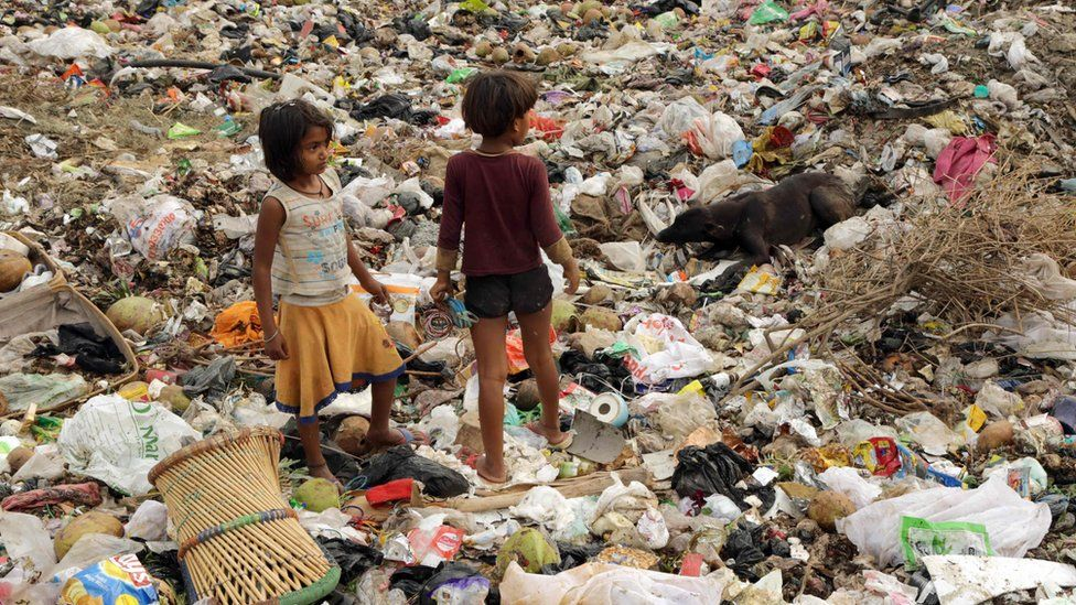 Indian child rag pickers search for recyclable materials at a garbage dump area in Noida on May 14, 2018.