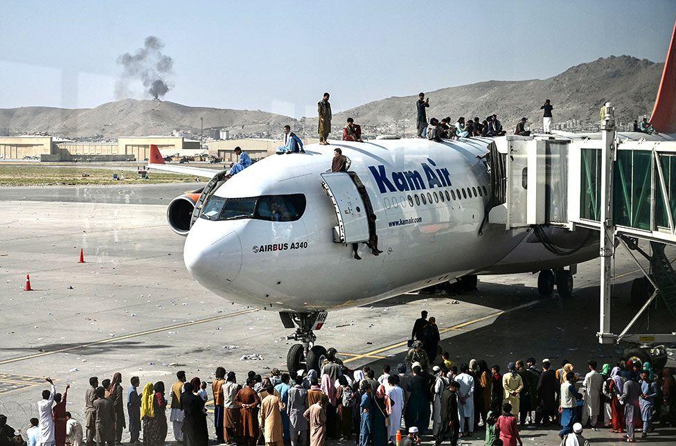 Οι Αφγανοί ανεβαίνουν πάνω σε ένα αεροπλάνο καθώς περιμένουν στο αεροδρόμιο της Καμπούλ στις 16 Αυγούστου 2021
