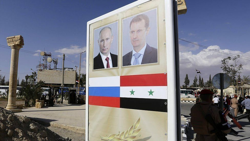 A poster bearing a portrait of Syrian President Bashar al-Assad (R) and Russian President Vladimir Putin is seen ahead of a music concert in the ancient theatre of Syria's ravaged Palmyra on May 6 2016.