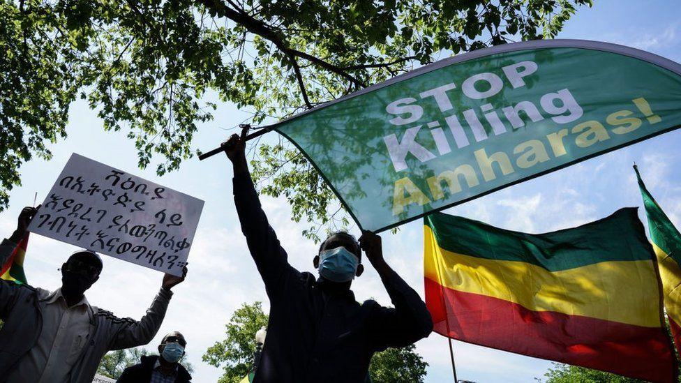 Des membres de la communauté éthiopienne brandissent des pancartes au département d'État américain pour protester contre le meurtre et le nettoyage ethnique en cours de membres de l'ethnie amhara dans plusieurs régions d'Éthiopie au département d'État américain le 17 mai 2021 à Washington, DC.