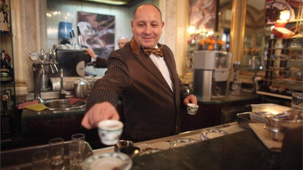 A barista serves coffee in Naples, Italy
