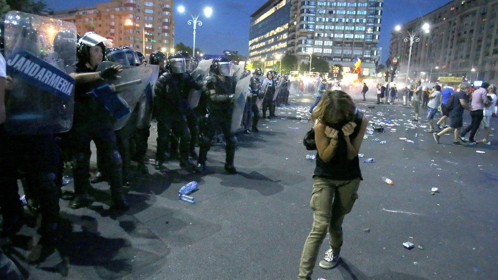 A woman ducks away from riot police in Romania