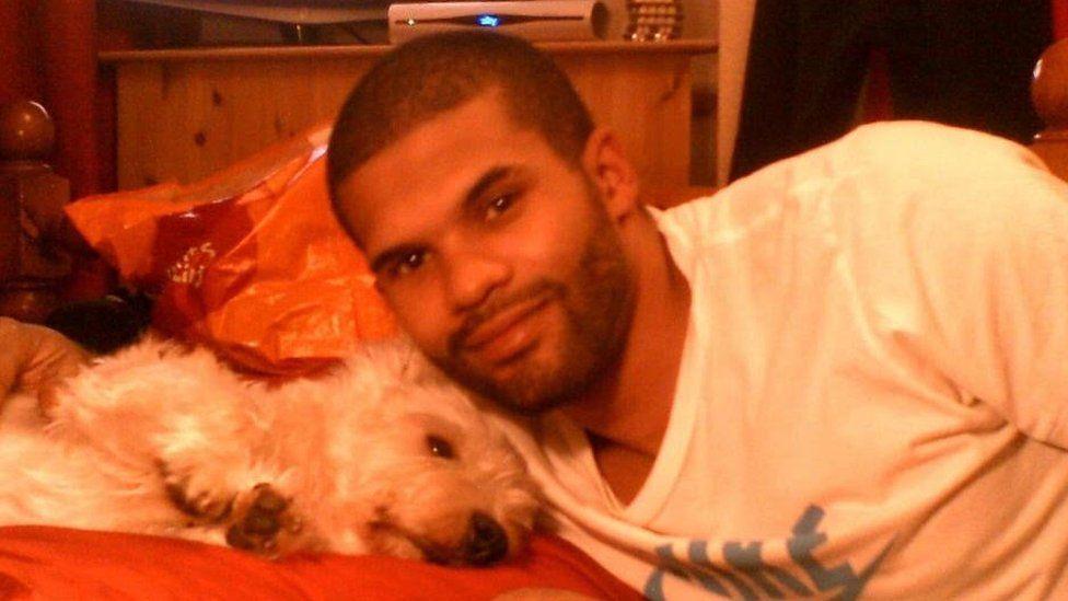 Simeon Francis lying next to a dog