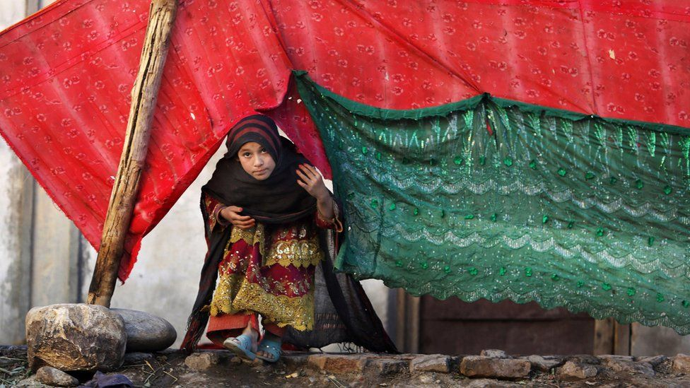 In this Sunday, Nov. 29, 2015 photo, an internally displaced girl peeks from a tent after her family left their village in Rodat district of Jalalabad east of Kabul