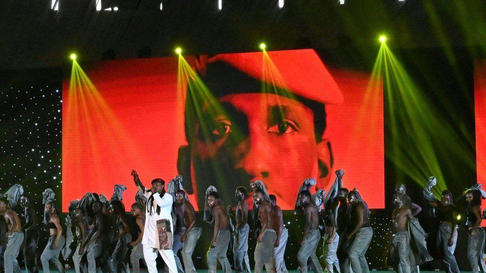 Группа выступает на сцене на фоне большого изображения Томаса Санкары