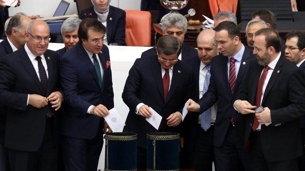 Prime Minister Ahmet Davutoglu, center, and his ruling party legislators vote at the parliament in Ankara, Turkey