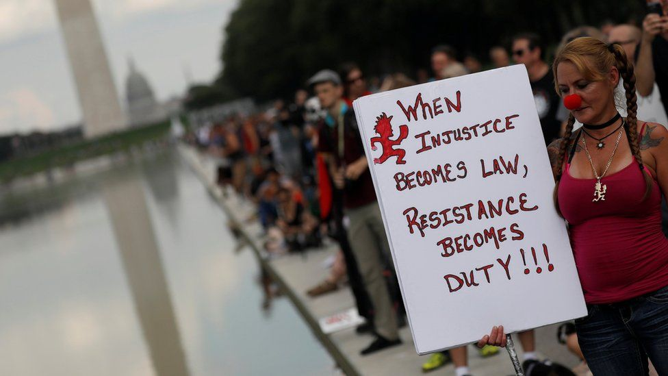 """A woman holds up a sign saying """"when injustice becomes law, resistance becomes duty"""" during a march in Washington"""