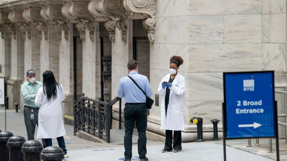 Employees screened by healthcare workers before entering the New York Stock Exchange, which partially reopened in late May