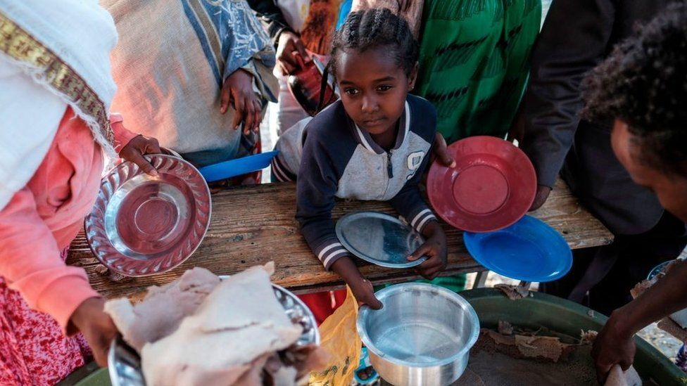 A displaced child from Western Tigray waits at meal time to receive a plate of food outside a classroom in the school where they are sheltering in Tigray's capital Mekele on February 24, 2021.