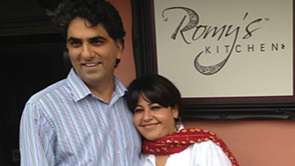 Romy Gill standing outside her restaurant with her husband