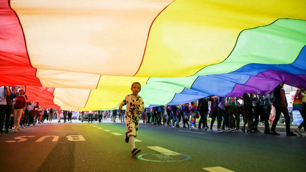 File photo of a child running underneath a rainbow