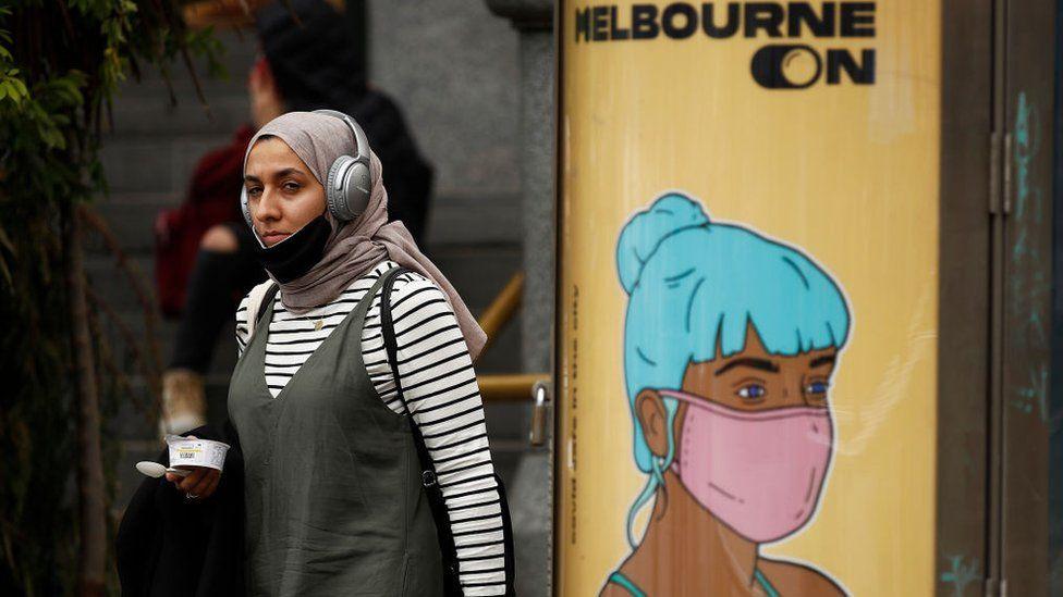 Молодая женщина в маске и хиджабе проходит мимо столба с рекламой, на которой изображена женщина с синими волосами в маске.