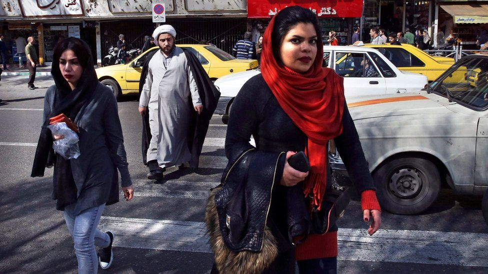 Pedestrians cross a square a day after parliamentary and Experts Assembly elections in Iran, Saturday, Feb. 27, 2016