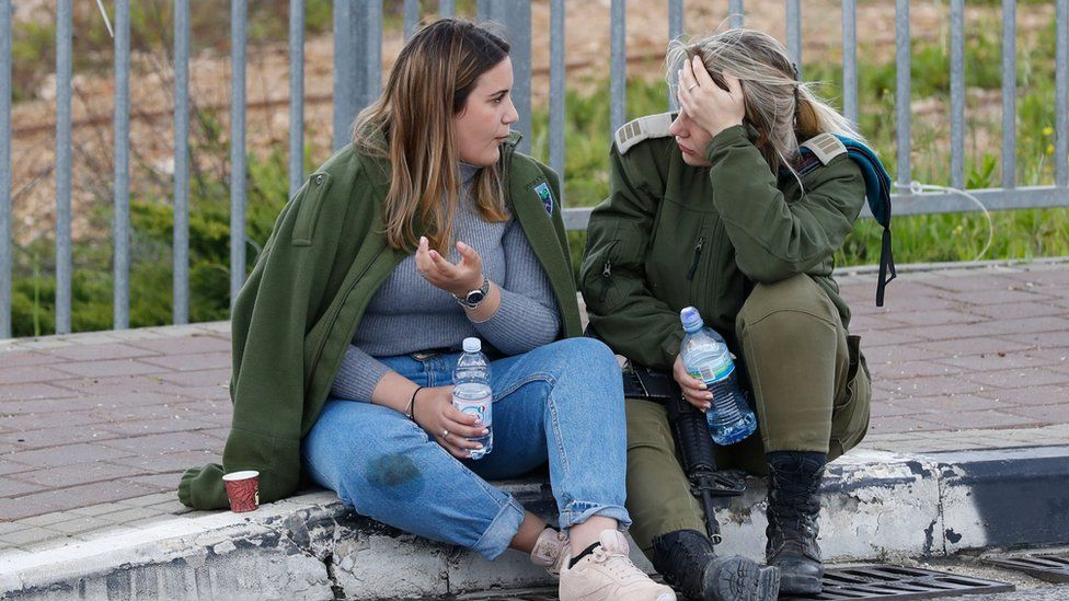 An Israeli soldier speaks to a woman at the scene of a deadly attack near the Jewish settlement of Ariel in the occupied West Bank (17 March 2019)