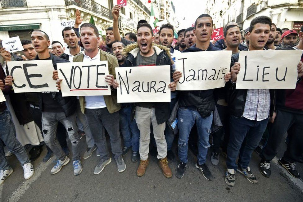 """Algerian demonstrators on 6 December carry placards that read in French: """"This vote will never happen""""."""