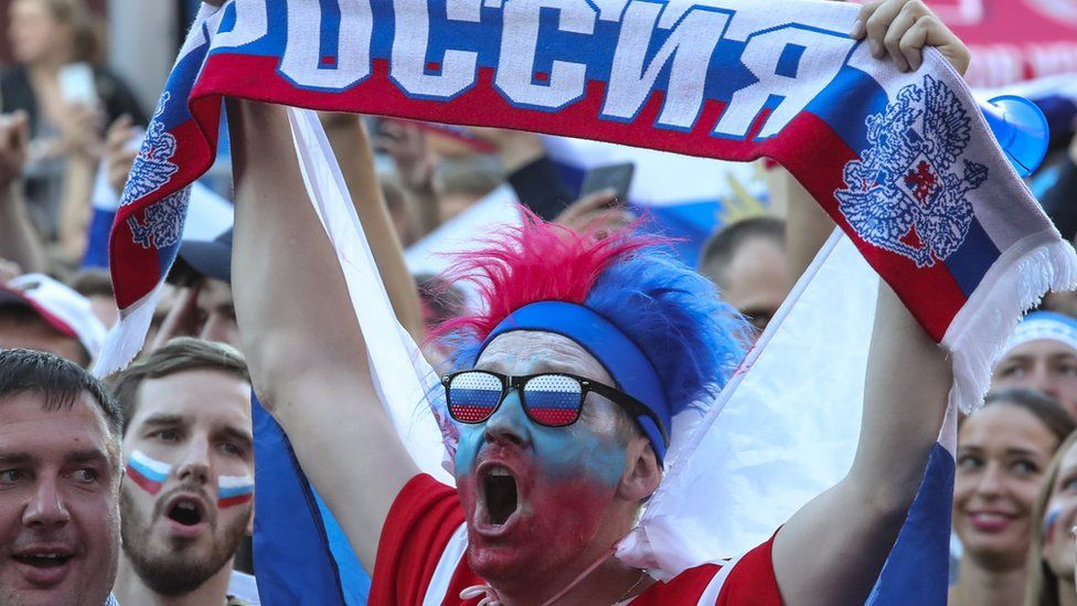 A fan raises a Russia scarf at the FIFA World Cup 2018 quarter final in St Petersburg, 7 July 2018