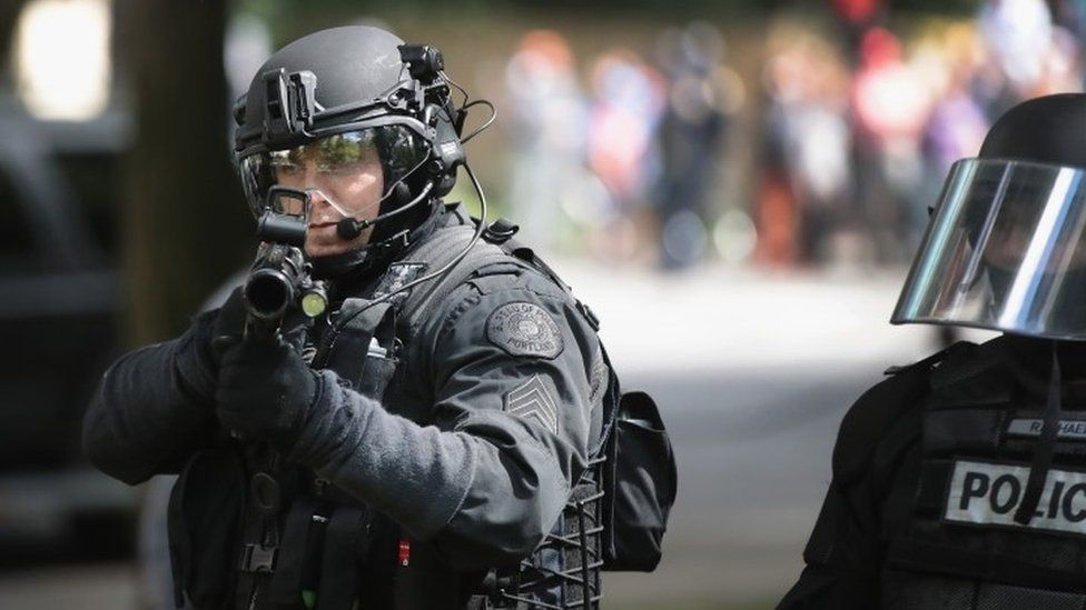 A police officer shoots non-lethal rounds at demonstrators in Portland (04 June 2017)