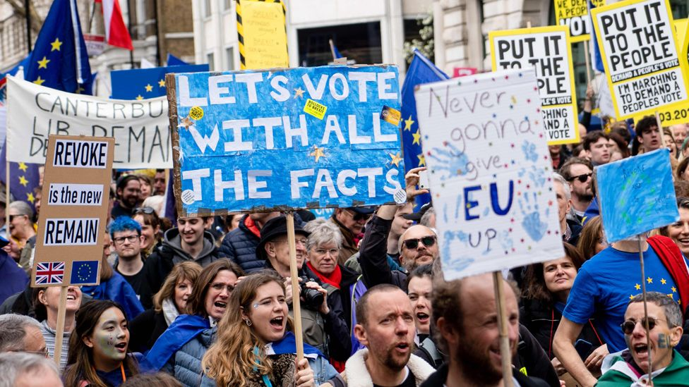 People hold placards during Saturday's pro-EU march through London organised by the People's Vote campaign