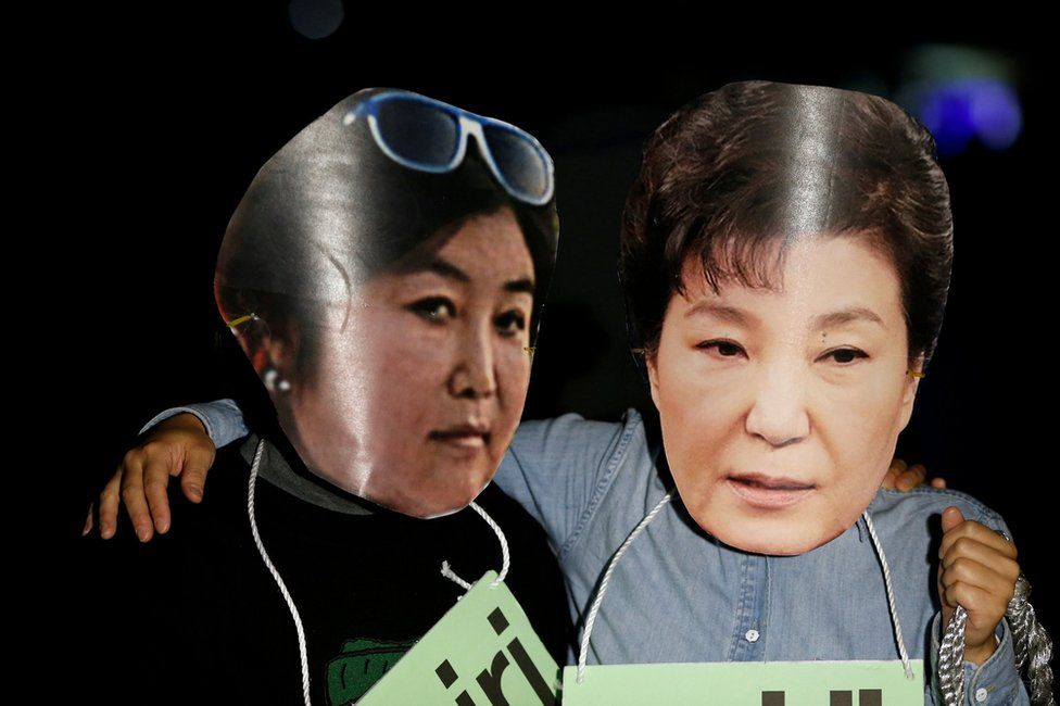 Protesters wearing cut-outs of South Korean President Park Geun-hye (R) and Choi Soon-sil attend a protest denouncing Park over a recent influence-peddling scandal in central Seoul, South Korea, 27 October 2016.