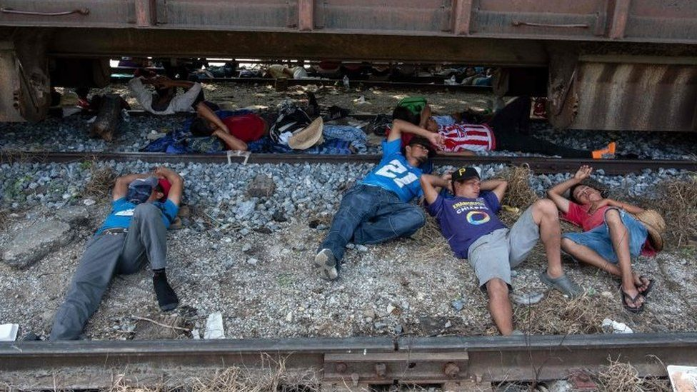 Migrants from the caravan rest on rail tracks in Arriaga, Mexico. Photo: 26 October 2018
