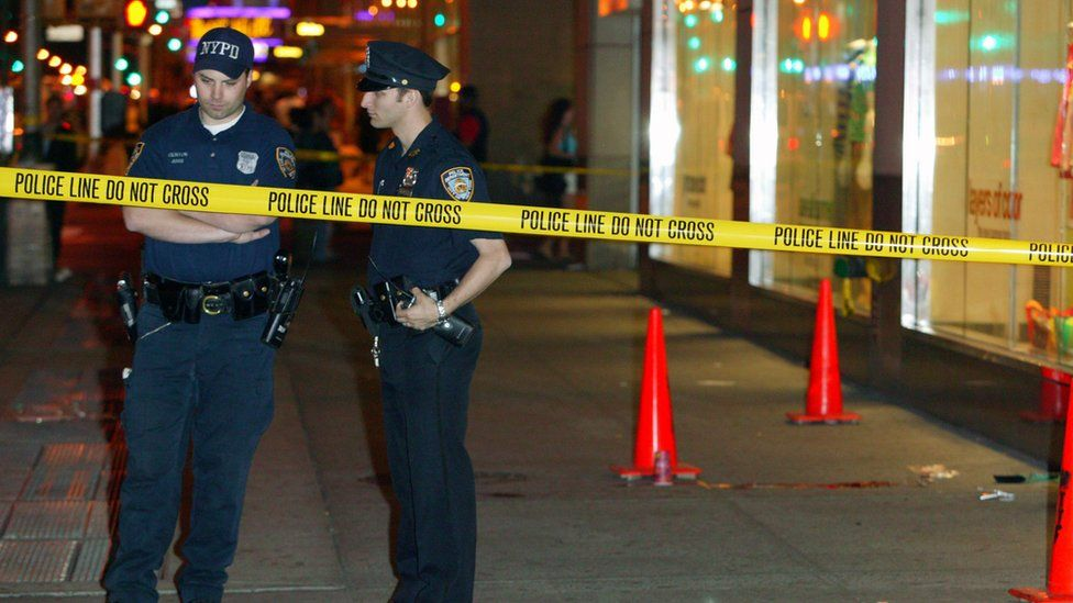 Two New York police officers standing behind crime scene tape