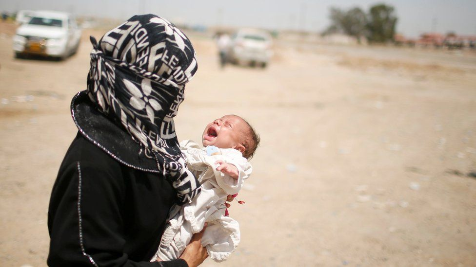A displaced Iraqi holds her baby while she moves to a safe place as Iraqi forces battle Islamic State militants in western Mosul (10 May 2017)