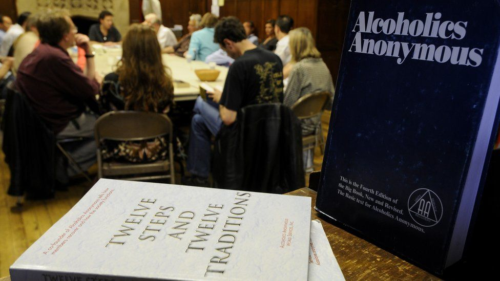 A group of people attend and AA meeting with AA literature in the foreground