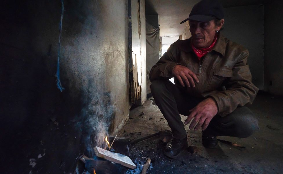 Derrick Brown crouches over trying to get a fire started to make coffee for himself and a friend in the derelict San Jose building in Johannesburg, South Africa