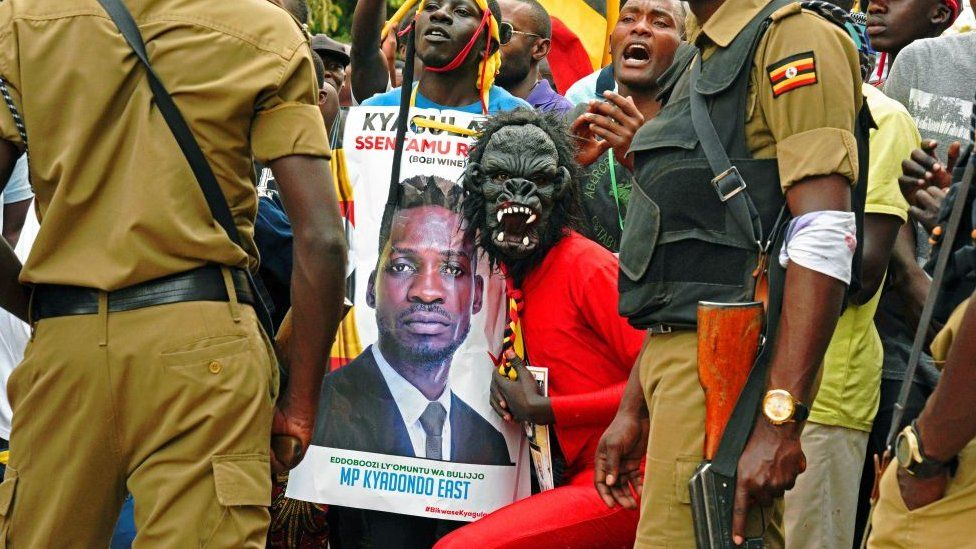 Bobi Wine supporters pose with his poster