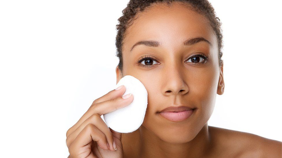 A woman removing makeup