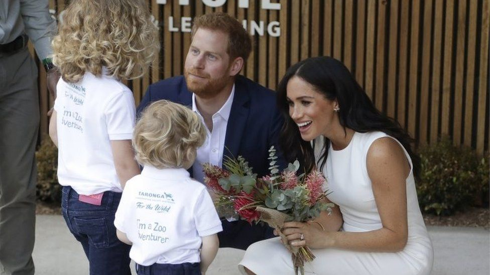 The Duke and Duchess of Sussex receive native flowers from Finley Blue and Dasha Gallagher at Taronga Zoo in Sydney, Australia