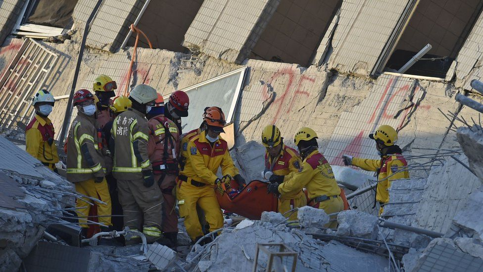 Rescuers bring out an eight-year old girl survivor to waiting personnel after she was rescued from the rubble at the Wei-Kuan complex which collapsed in the 6.4 magnitude earthquake, in the southern Taiwanese city of Tainan on February 8, 2016. T