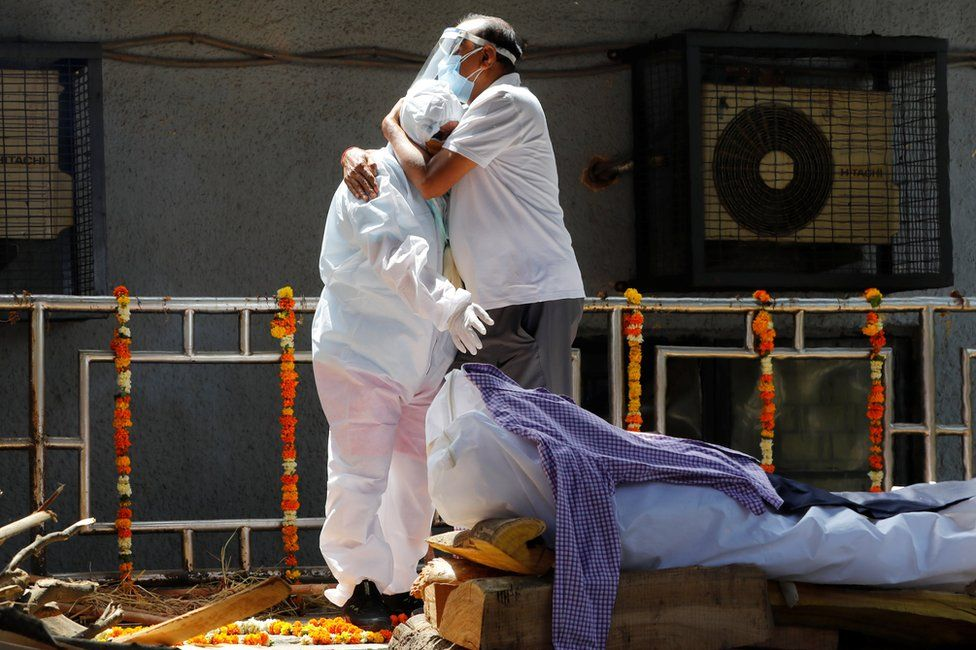 Relatives wearing personal protective equipment (PPE) mourn next to the body of a relative in New Delhi, India