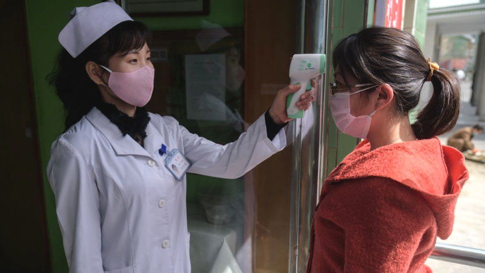A health worker takes the temperature of a woman