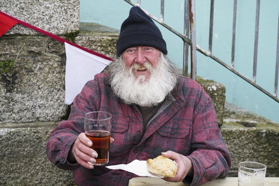 A man holds a pint of beer and a pasty