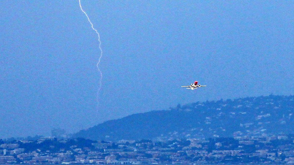 A plane takes off from Nice airport in France as lightning strikes, 5 June 2011