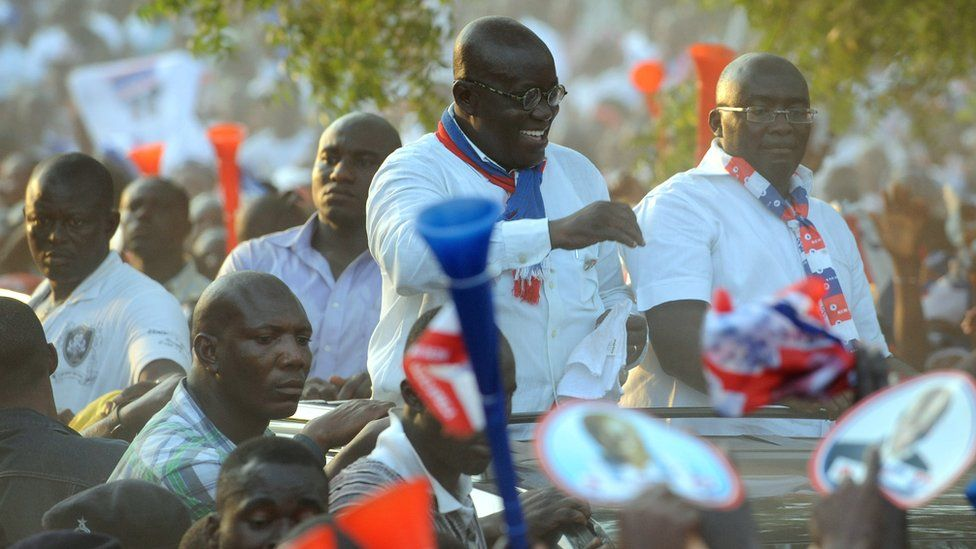Nana Akufo-Addo greets party supporters from an open-top vehicle.