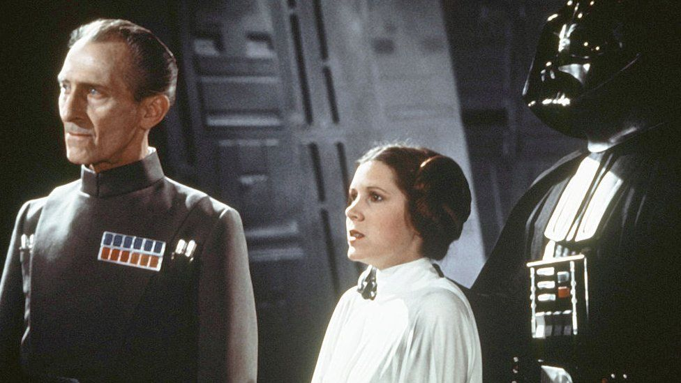 British actors Peter Cushing, David Prowse, and American actress Carrie Fisher on the set of Star Wars: Episode IV - A New Hope in 1977