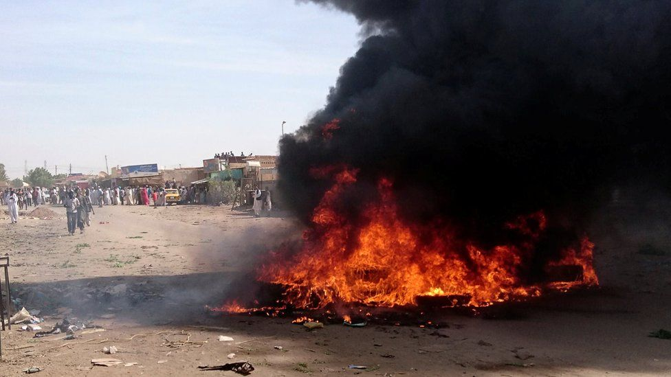 A fire is lit along the street during protests against price increases in Atbara, Nile River state, Sudan, 20 December 2018