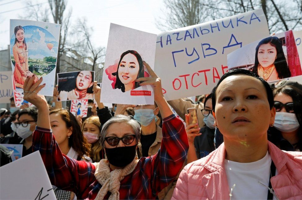 People hold placards during a rally in front of Kyrgyzstan's interior ministry after the murder of Aizada Kanatbekova