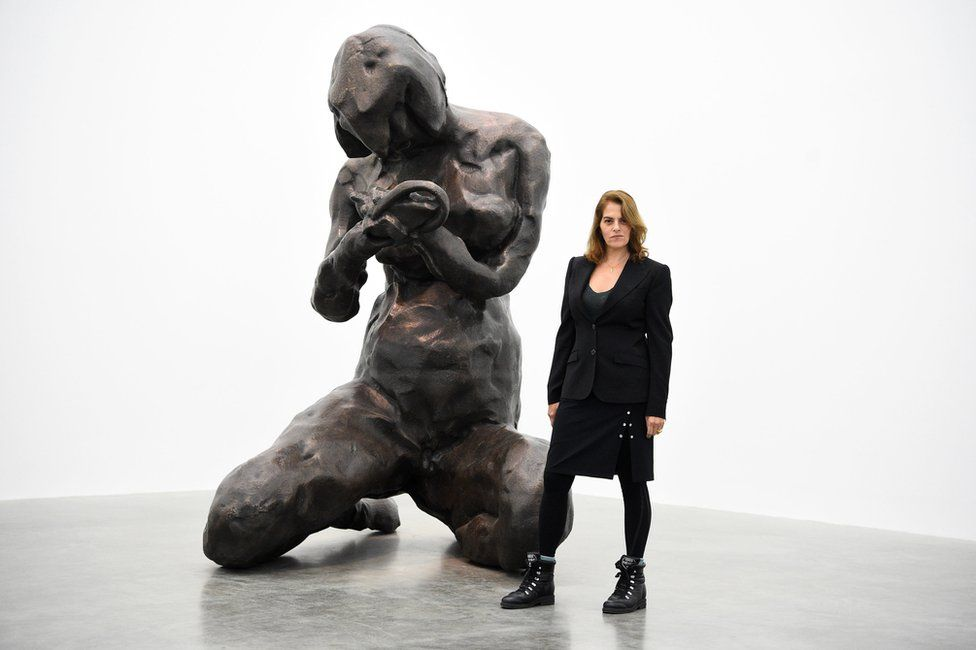Artist Tracey Emin standing next to a large bronze sculpture of a female figure