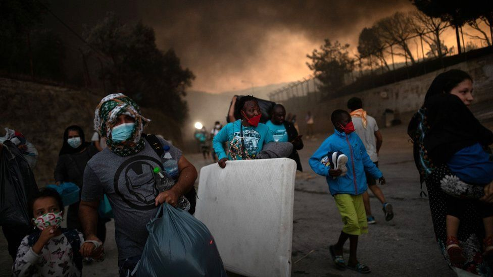 Refugees and migrants carrying their belongings flee a fire burning at the Moria camp on the island of Lesbos, Greece, 9 September 2020