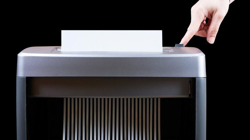 A man shredding paper